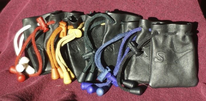 Drawstring colors: white, red, orange, yellow, green, blue, purple, black. Not shown: brown(see 'camel' bag in previous picture), gray. The manufacturer says they can provide a brighter green than the one shown here, which looks black in normal light.