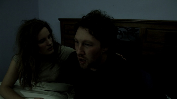 Aaron (Barrett Lione-Seaton) wakes from a nightmare, as Kim (Robin James) consoles him.