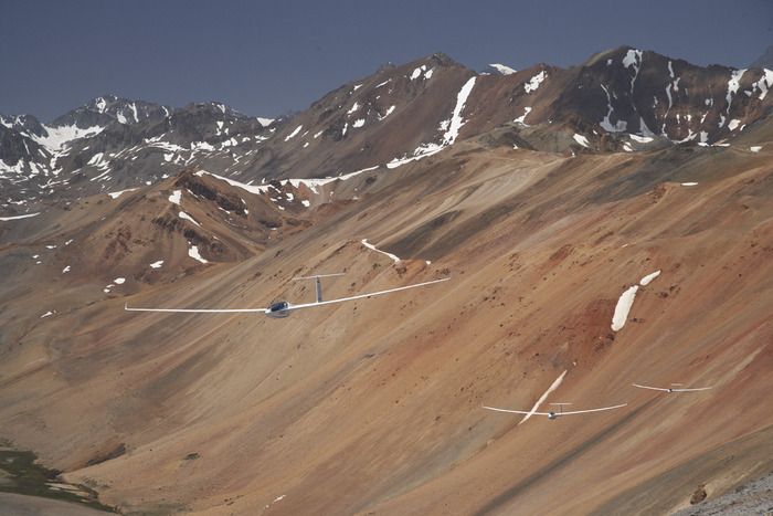 "Battle for the lead in ""Sailplane Grand Prix in the Andes"", against a backdrop of the typical copper-coloured Chilean mountain range"