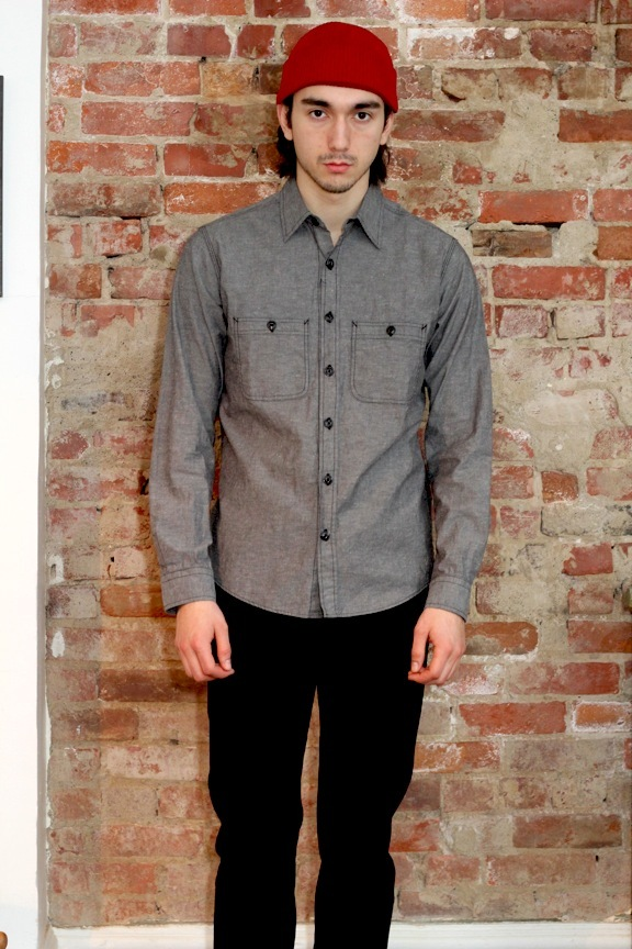 """Utility"" shirt in black Japanese 100% cotton chambray.  Double needle chain stitch, single straight stitch construction. Bar tacking at points of strain Gusseted side seams. Black cats eye buttons."