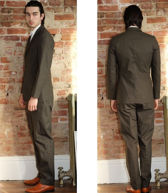 """Jimmy"" trouser in slate brown Japanese 100% slub cotton hopsack. Black plain weave poplin contrasting pocket bags and waist band. Cats eye button fly. 2 slash front pockets and 2 back pockets. 1 with cats eye button closure. Cuffed hem."