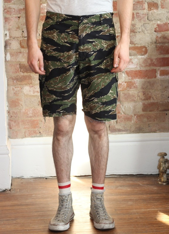 """Tiger"" short in ""Tigerstripe Products"" Vietnam tigerstripe camouflage in rip stop cotton. Double needle chain stitch and single straight stitch construction. Bar tacking at points of strain. Keyhole button holes. Zipper fly. Cats eye buttons. Adjustable"