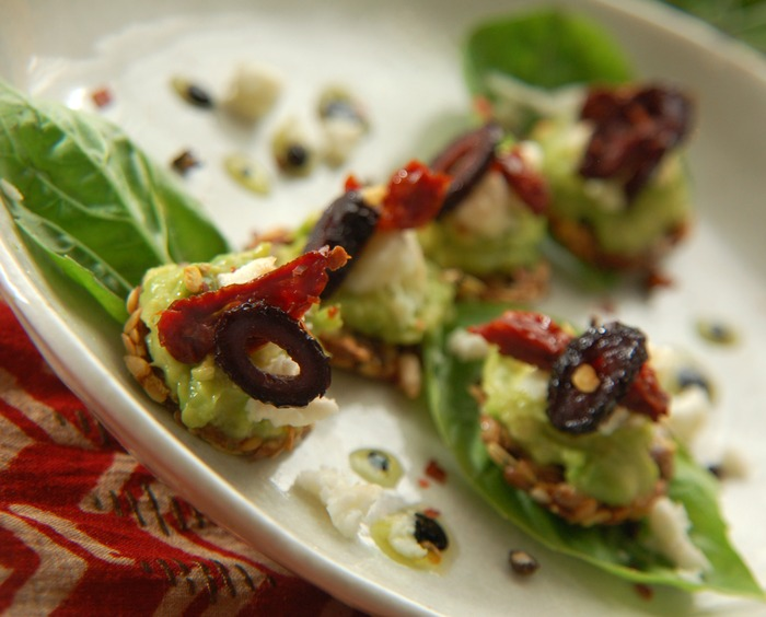 Raw bruschetta: raw goat milk feta, basil, sundried tomatoes and botija olives on an herbed flax & sunflower seed cracker