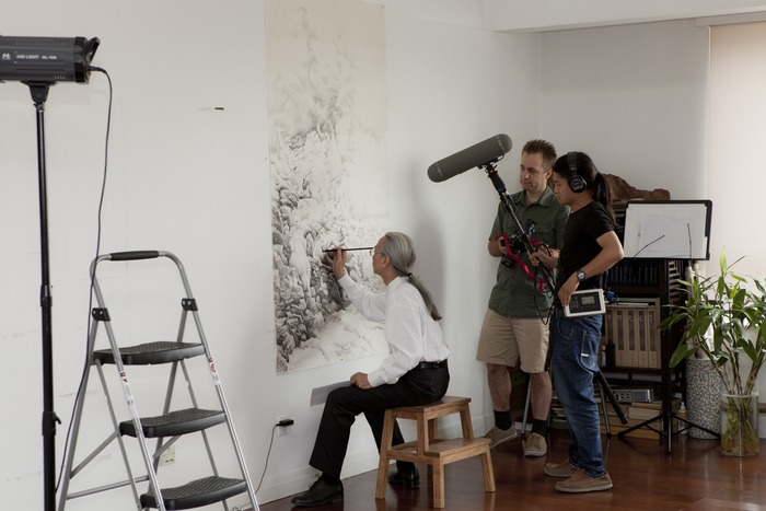 Undeterred by the film crew, Liu Dan works on a landscape. I am honored and grateful that the artists allowed us the privilege of observing their creative process. (Photo copyright ©2012 Britta Erickson)