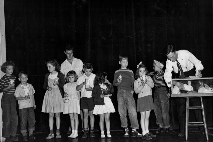 Children from the community participating on stage at the Priest Theatre for an Easter event.