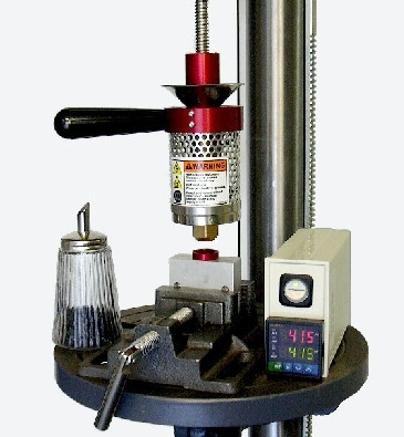 This is a photo of our original plastic injection machine mounted in a home drill press.