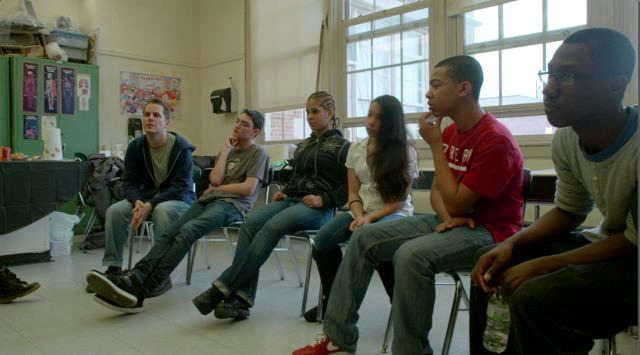 Cast members with Director Jeremy Engle share their own high-school experiences in a rehearsal.