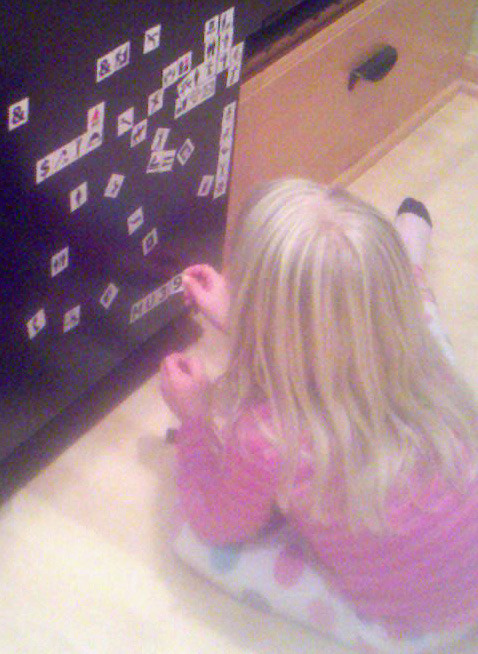 Kids play with symbol fridge magnets creating stories while learning