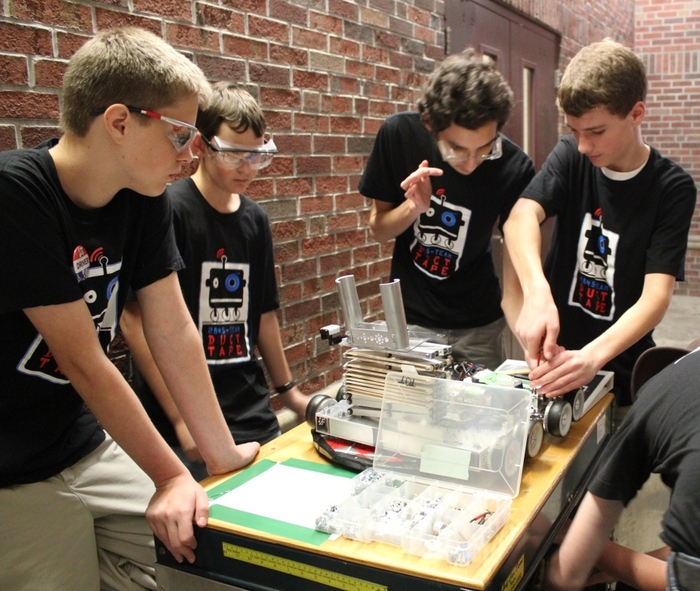 The TDT mechanical team performs a little hallway robot surgery between matches at a competition.