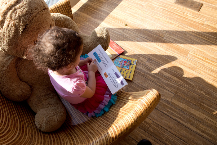 My daughter reading the book to Winnie-the-Pooh at the library