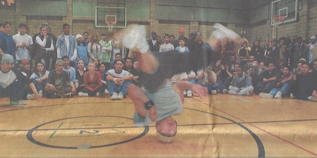 This is a newspaper clipping from the Anchorage Daily News front page article of Supply the Skillz 1. B-Boy Xpreshun doing a headspin in the competition.