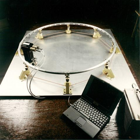 "The first Slingatron was a table-top sized model used to demonstrate the physics of phase-locking of a rolling ball bearing  inside the ""hula-hoop"" structure. This was quite successful and early patents were based partly on this demonstration."