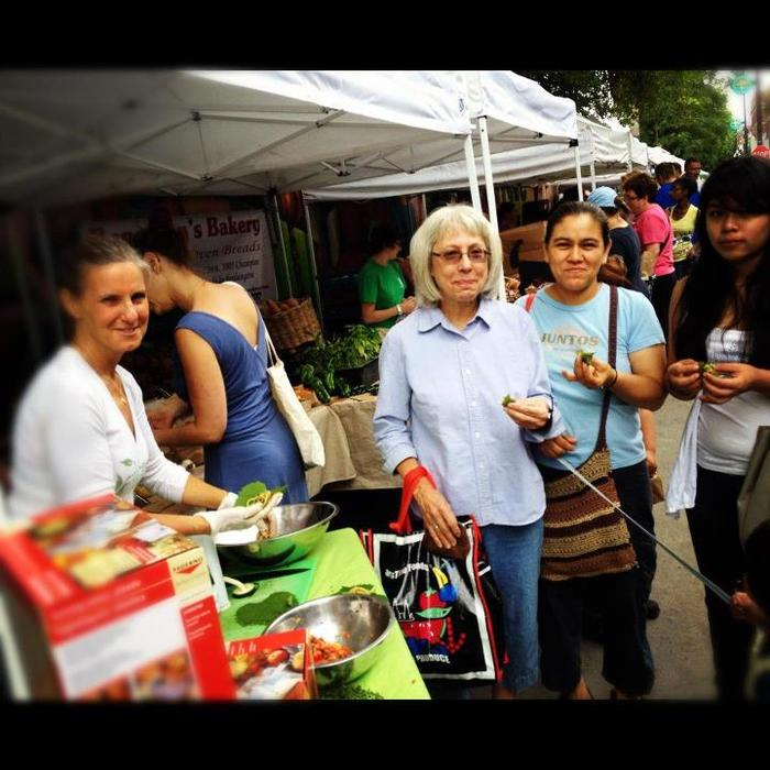 A food artisan sharing her cuisine with market shoppers