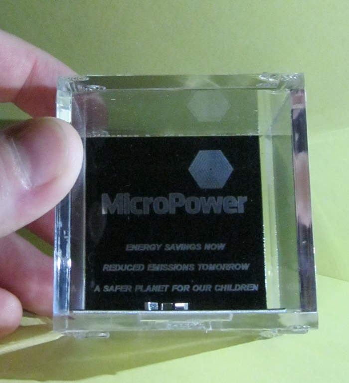 "Three MicroPower Chips in a Display Cube (2"") with inscription ""Energy Savings Now. Reduced Emissions Tomorrow. A Safer Planet For Our Children."""