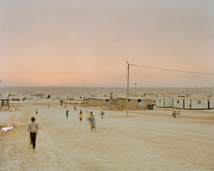 Kids run home at dusk in Zaatari refugee camp.