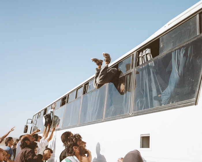 A man dives through an open window into a bus returning to Syria from Zaatari refugee camp.