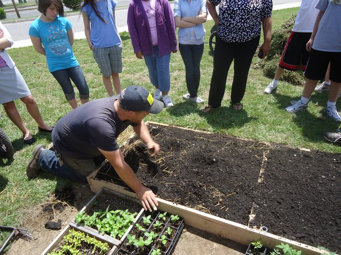 Co-owner Clark Lovelady leads a class of middle-schools or spring vegetable planting techniques