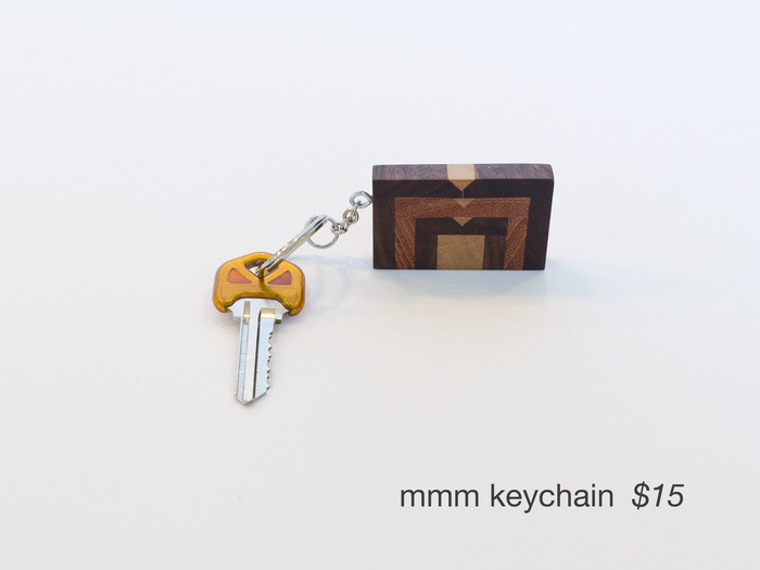 Crafted from a mix of woods, this keychain features the MMM logo. (key to our shop not included)