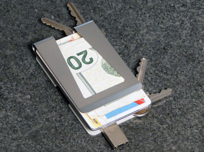 KeyClip shown with four keys, USB drive, cash, credit cards and ID