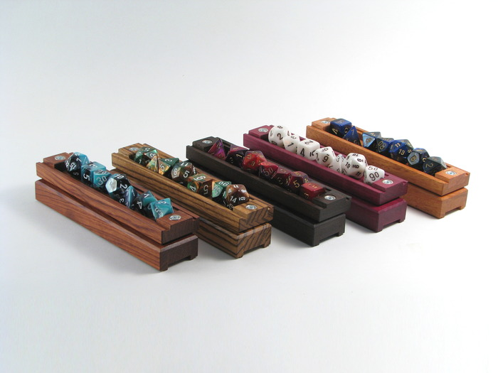(Left to right:) Bubinga with Shell dice set, Zebrawood with Copper/Green dice set, Wenge with Red/Purple dice set, Purpleheart with Mother of Pearl dice set, Mahogany with Blue/Black dice set.