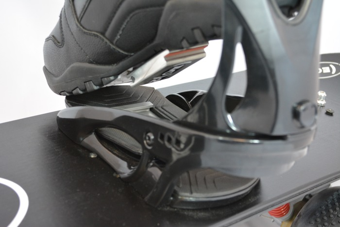 Rear view angle of approach for attaching boots to snowboard binding.  Engagement is similar to clip-in pedals for cycling and mountain biking.