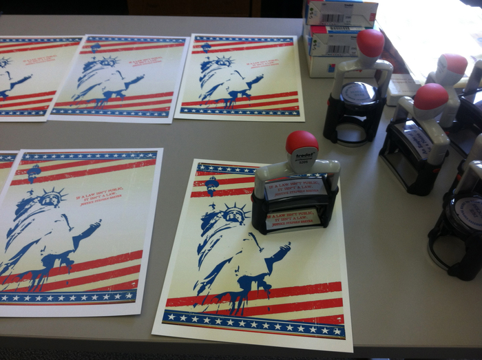 "Step 1. Cover sheets are prepared with the Statue of Liberty. A Trodart self-inking red rubber stamp is used to stamp ""If a law isn't public, it isn't law"" on the front."