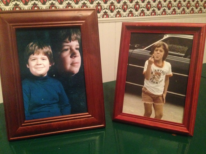 Framed portraits of stars as young men. Set props stolen from the set of NATURE CALLS.