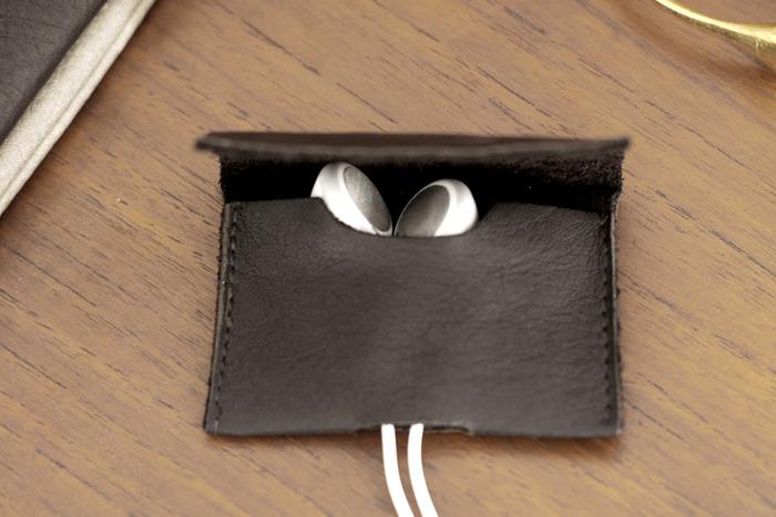 "EARBUD CASE cord organizer in chestnut brown. 2"" wide x 1.75"" high."