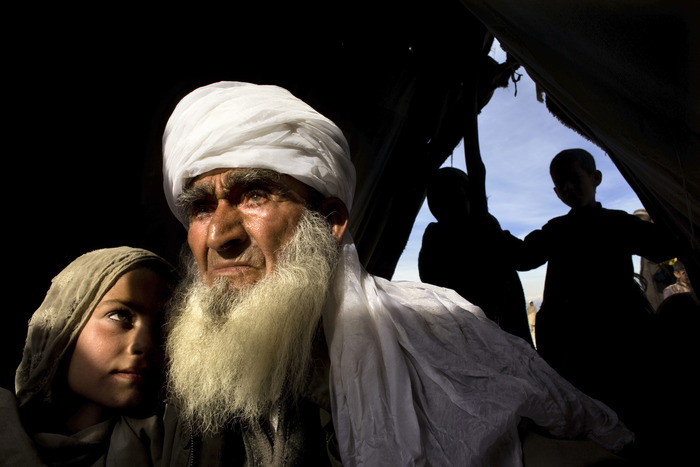 An elderly Afghan man holds his grand daughter at a makeshift refugee camp after their village was bombed.