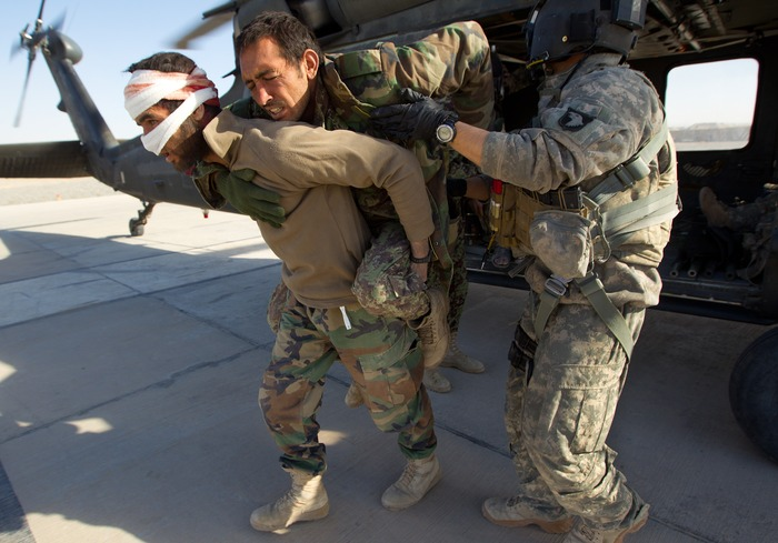 An Afghan soldier carries another wounded Afghan National Army comrade off a Blackhawk helicopter after they were rescued in an air mission in Kandahar.