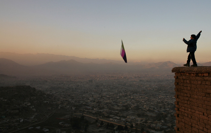 A boy flies a kite along a hill overlooking the city of Kabul at sunset. Kite flying was banned  under the Taliban rules for years.