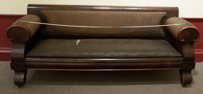 "The ""courting couch"" as it appeared before being sent to The Conservation Center, showing the wear and tear of its advanced age."