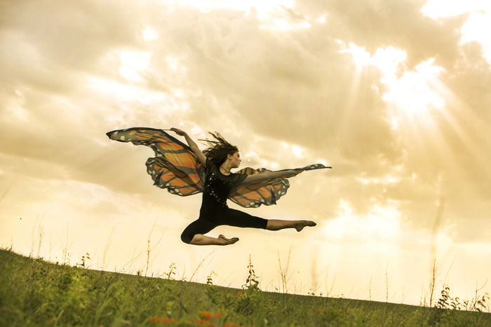 """In Flight,"" Vetter-Drusch jumps over an orange variety of milkweed and other prairie flowers that support monarchs and other pollinators. Photo by Jaime Schirmer for Moving for Monarchs"