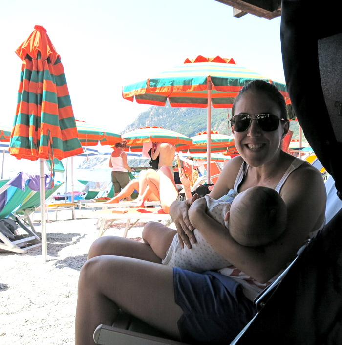Moon Mama founder, Gemma, forcing a smile while trying to breastfeed Hudson in Italy - this trip was a major catalyst for this invention