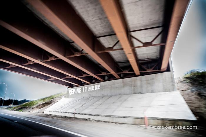 """Refine it here."" Graffiti on highway leading into the tar sands. Photo by Zack Embree"