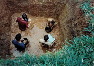 Students emptying water from a trash pit as a punishment