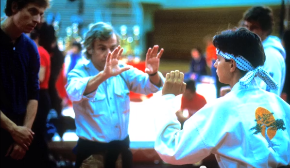"John G. Avildsen preparing a shot with Ralph Macchio on the set of ""The Karate Kid"" (1984)"