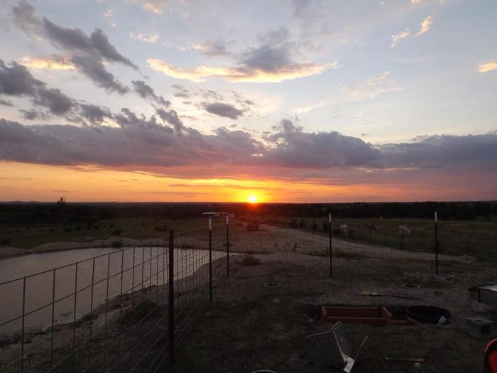 A Texas sunset at The Land. In the foreground is a memorial garden Jonathan's mom is building for him.