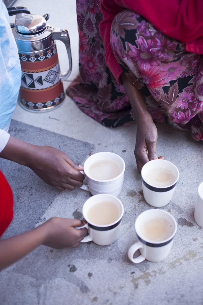 Halimo and daughters, from Somalia, share their spiced milk tea. (Photograph by Jennifer Martiné)