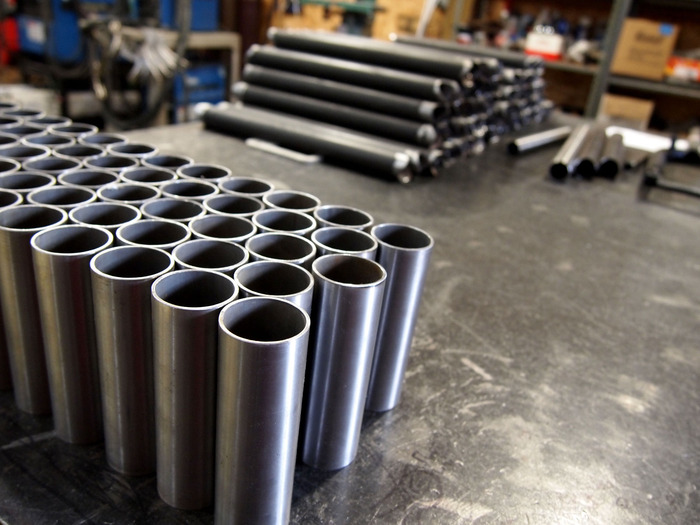 "Head tubes and ""tail"" tubes with a blurry pile of main tubes in the background, all ready to be assembled in the jig."
