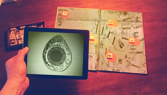 Using the iPad app to read the symbolic blocks placed on one of the maps in the book