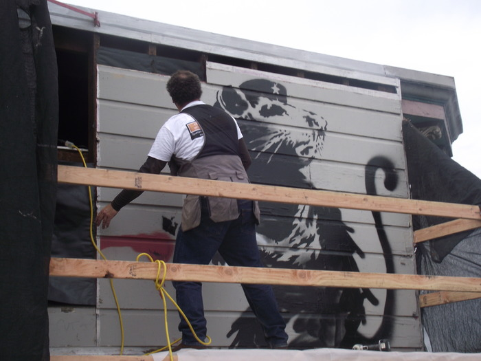 The Banksy is professionally removed piece by piece to ensure it's artistic viability for future public exhibition.