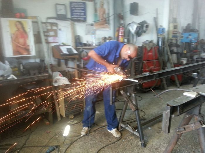 Pedro cutting and welding the handlebars
