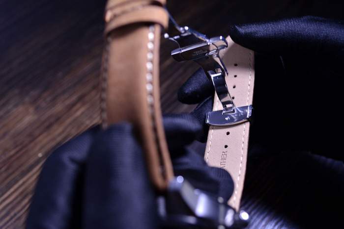 Fasten the clasp through the appropriate hole in the watch band, testing it on your wrist for correct fit.