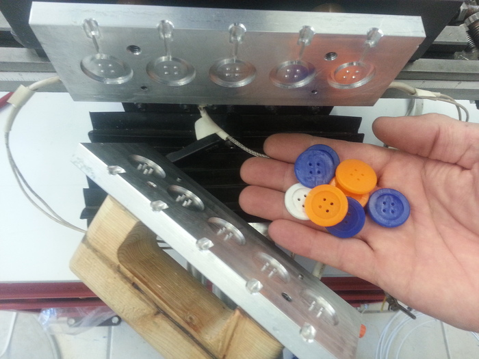 An open five cavity button mold and a small hand full of buttons that were molded with this mold on a TriBot machine.
