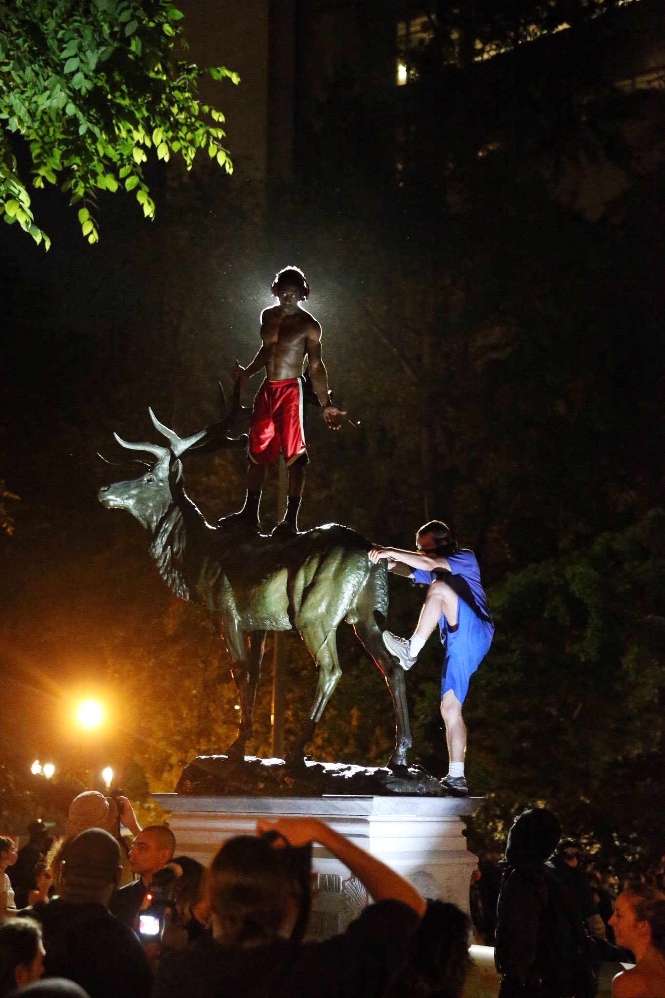 Man on elk statue reach out to other man climbing