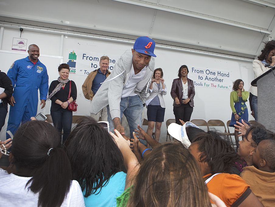 Pharrell Williams, three-time Grammy Award-winning producer from Virginia Beach, Va. reaches out to local students at Williams Farm Park, the site for his first Resource Center, which is supported by his foundation, From One Hand to Another (FOHTA). Credit: NASA/Sean Smith
