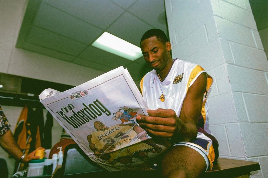 This image has an empty alt attribute; its file name is Kobe-Bryant-photographed-by-Andrew-D.-Bernstein-while-reading-the-paper-prior-to-playing-the-New-Jersey-Nets-during-the-2002-NBA-Finals-in-Los-Angeles-CA-June-01-2002-1024x682.jpg