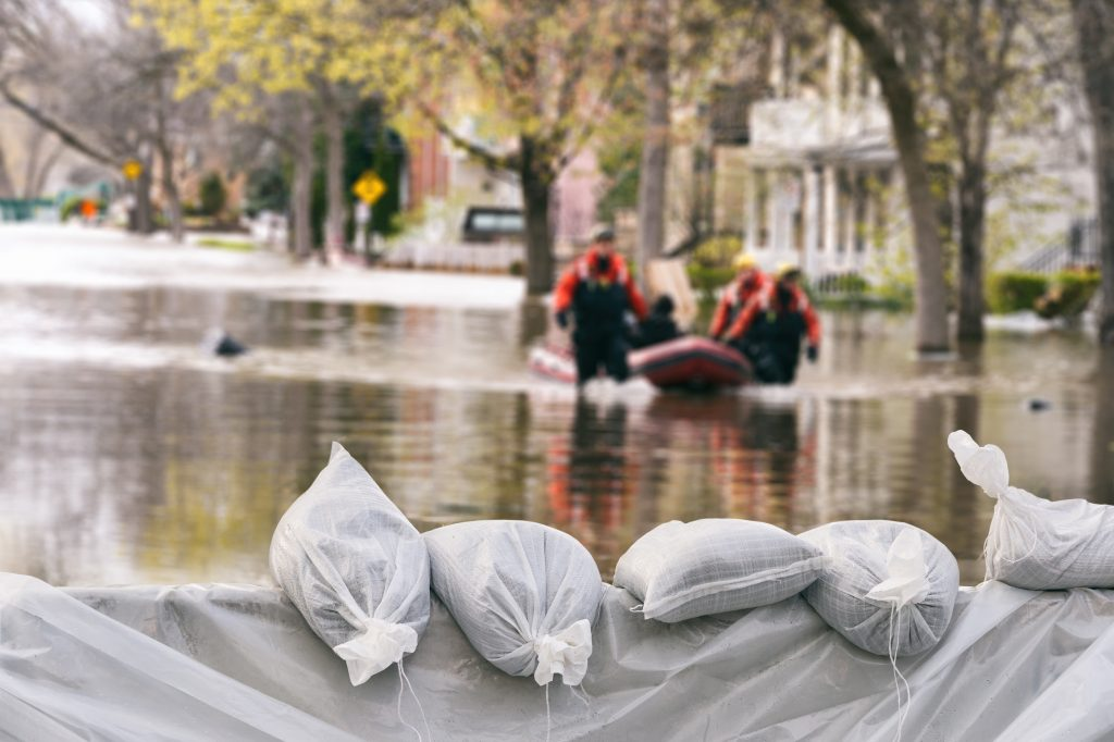 Flood Protection Sandbags with flooded homes 1024x682