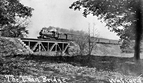 Iron bridge east of Watford with steam-powered train